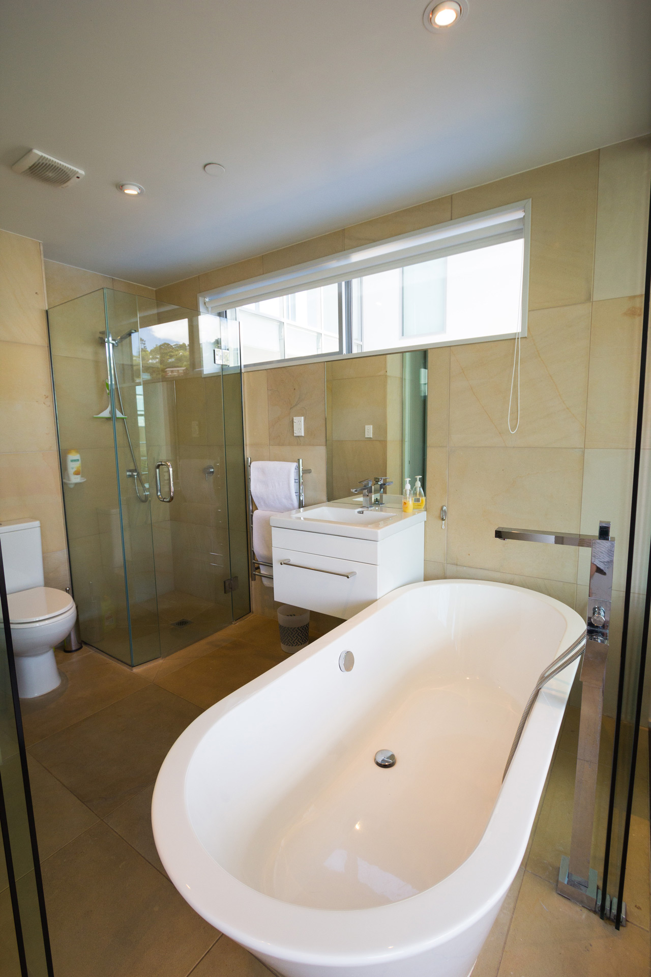 luxury ensuite with natural stone glass shower and grand freestanding bath